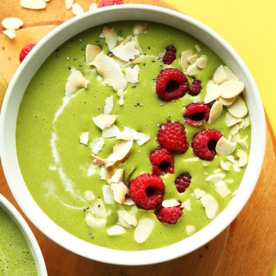 Matcha Green Smoothie Bowl topped with coconut flakes, slivered almonds, and fresh raspberries