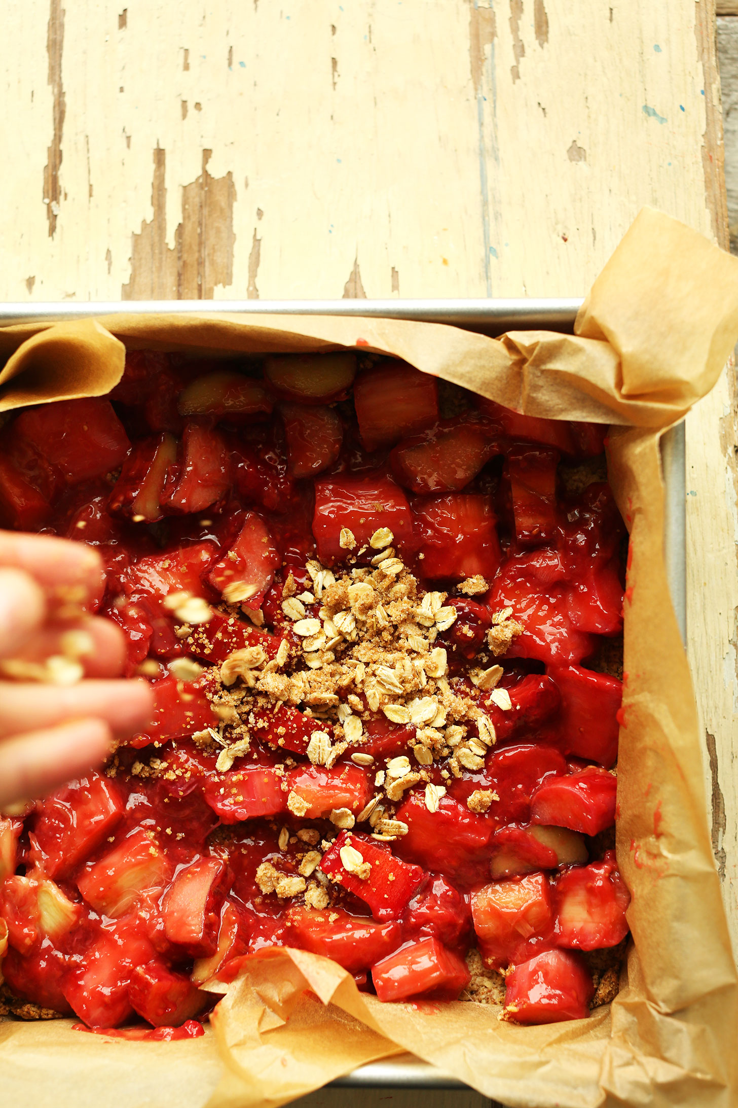 Sprinkle crumble topping onto our gluten-free vegan Strawberry Rhubarb Bars