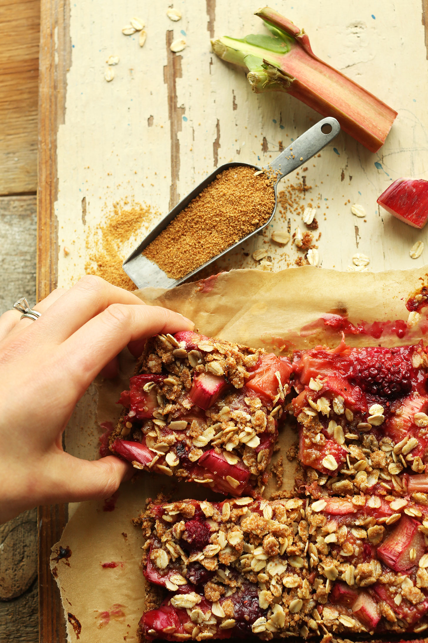 Grabbing a square of our Strawberry Rhubarb Crumble Bars recipe from the batch