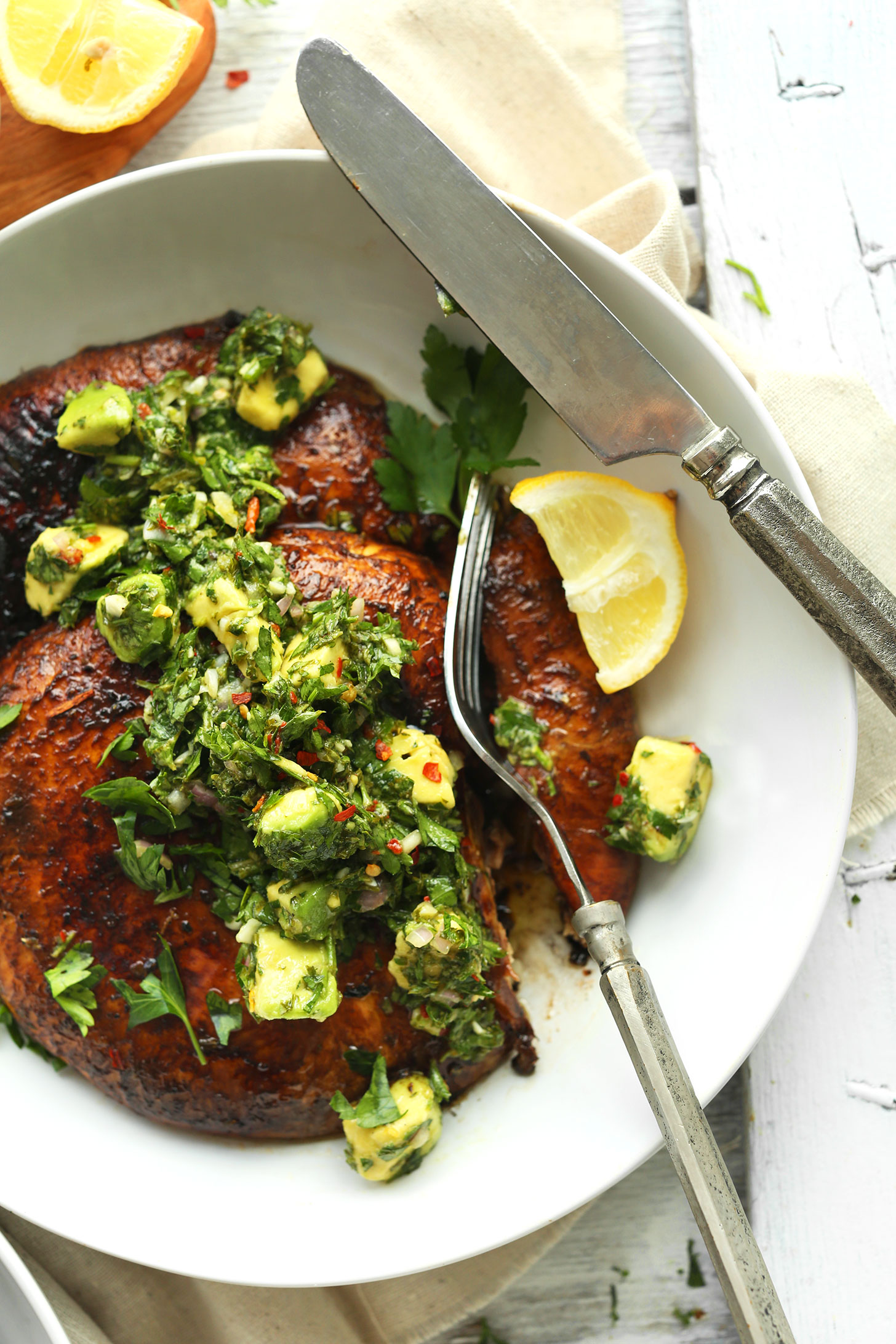 Using a fork to cut into a Grilled Portobello Steak with Avocado Chimichurri
