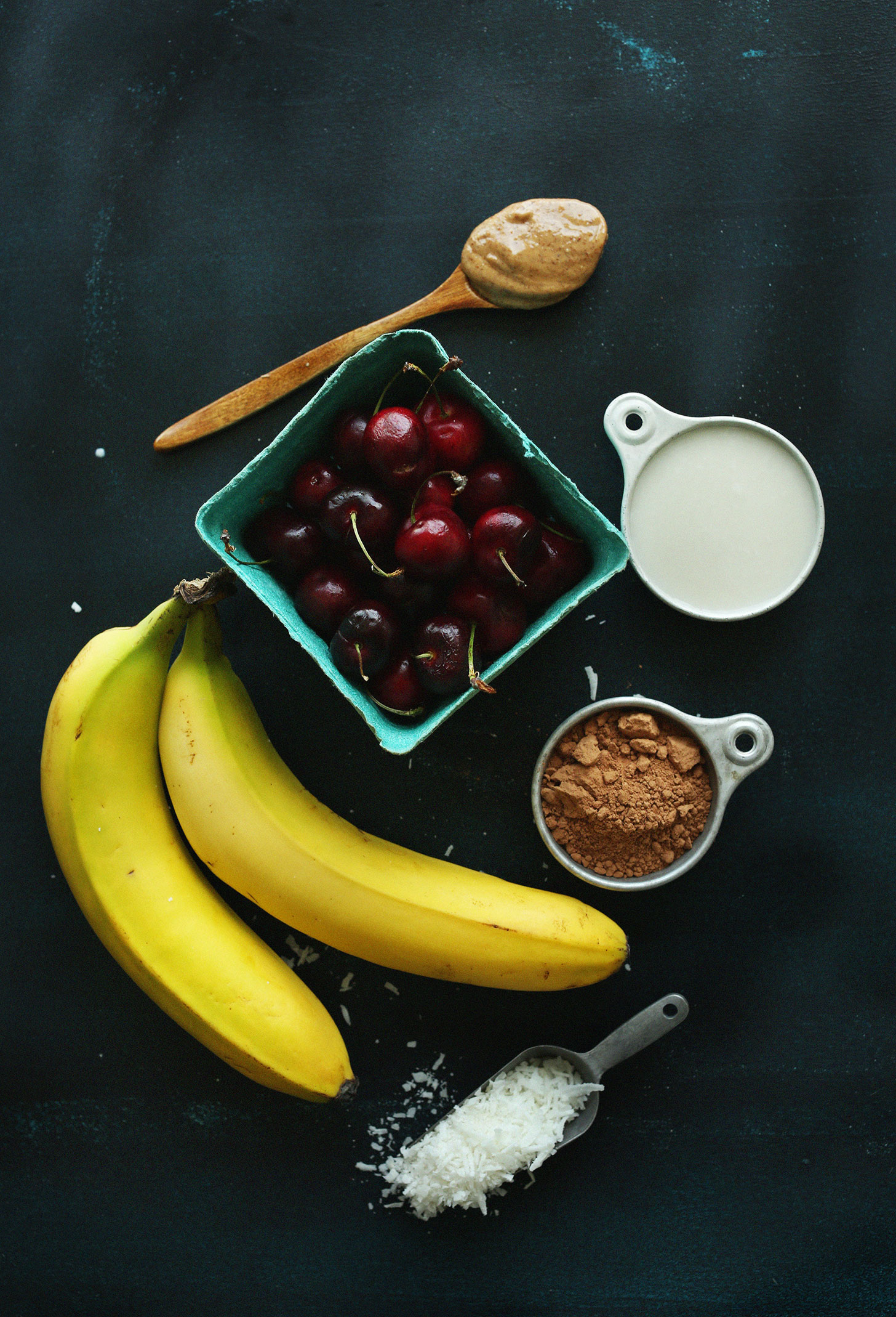 Nut butter, nut milk, cherries, bananas, cocoa powder, and shredded coconut for making our vegan Banana Split Smoothie