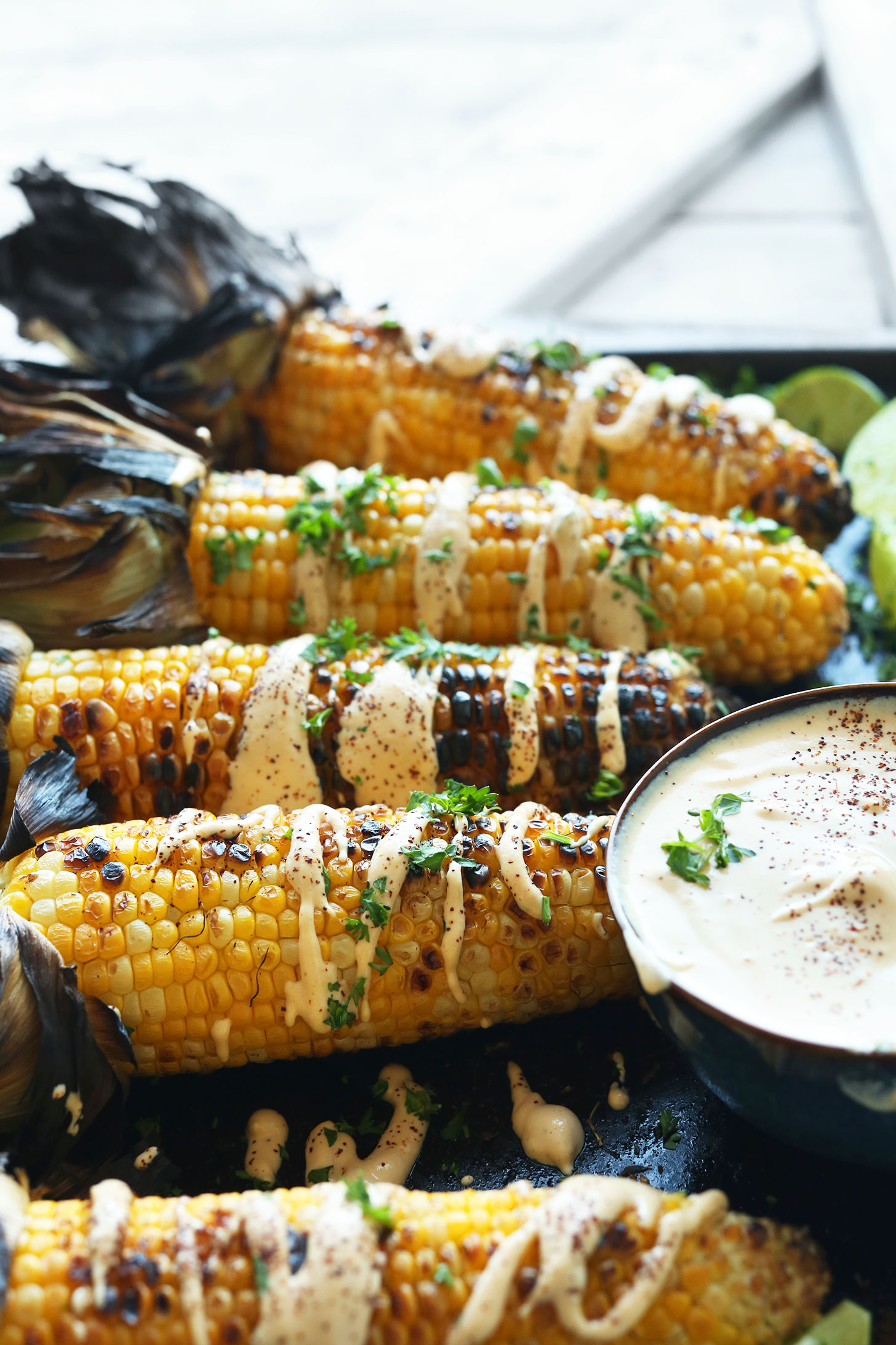 Cobs of Mexican Grilled Corn with a bowl of gluten-free vegan Sriracha Aioli
