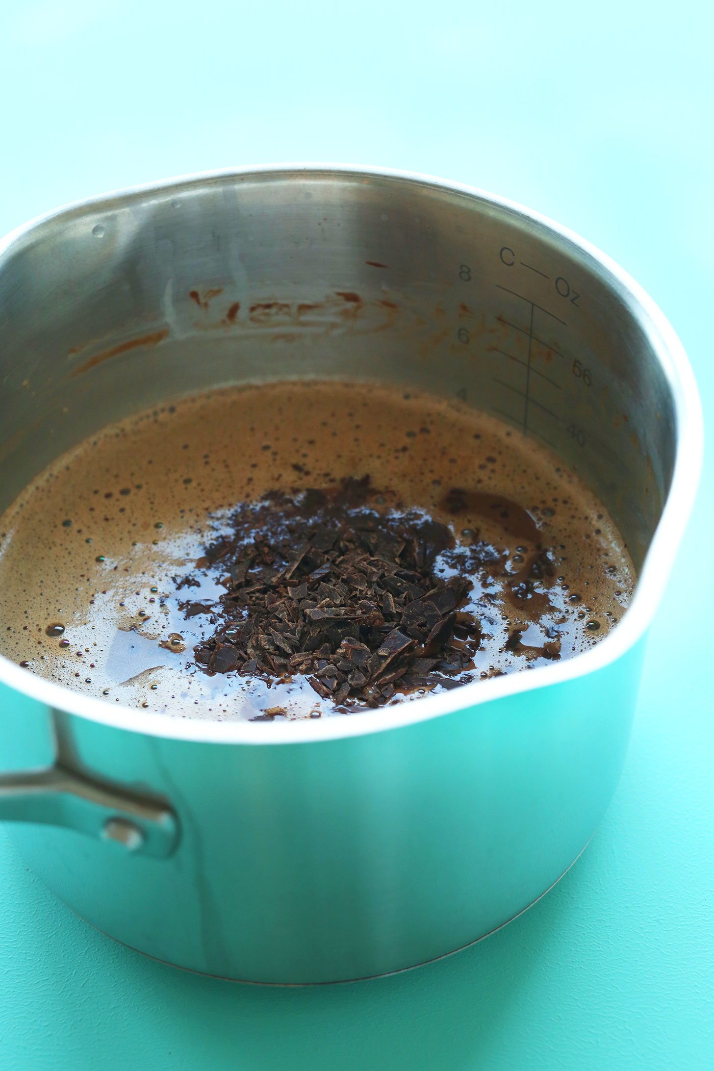 Adding chocolate shavings to a saucepan for homemade vegan chocolate ice cream
