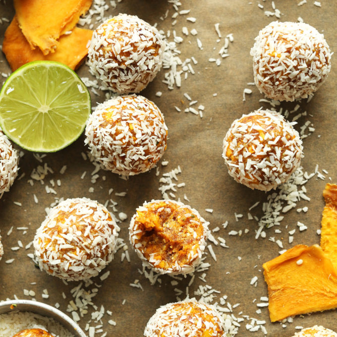 Gluten-free vegan Dried Mango Energy Bites on a parchment-lined baking sheet