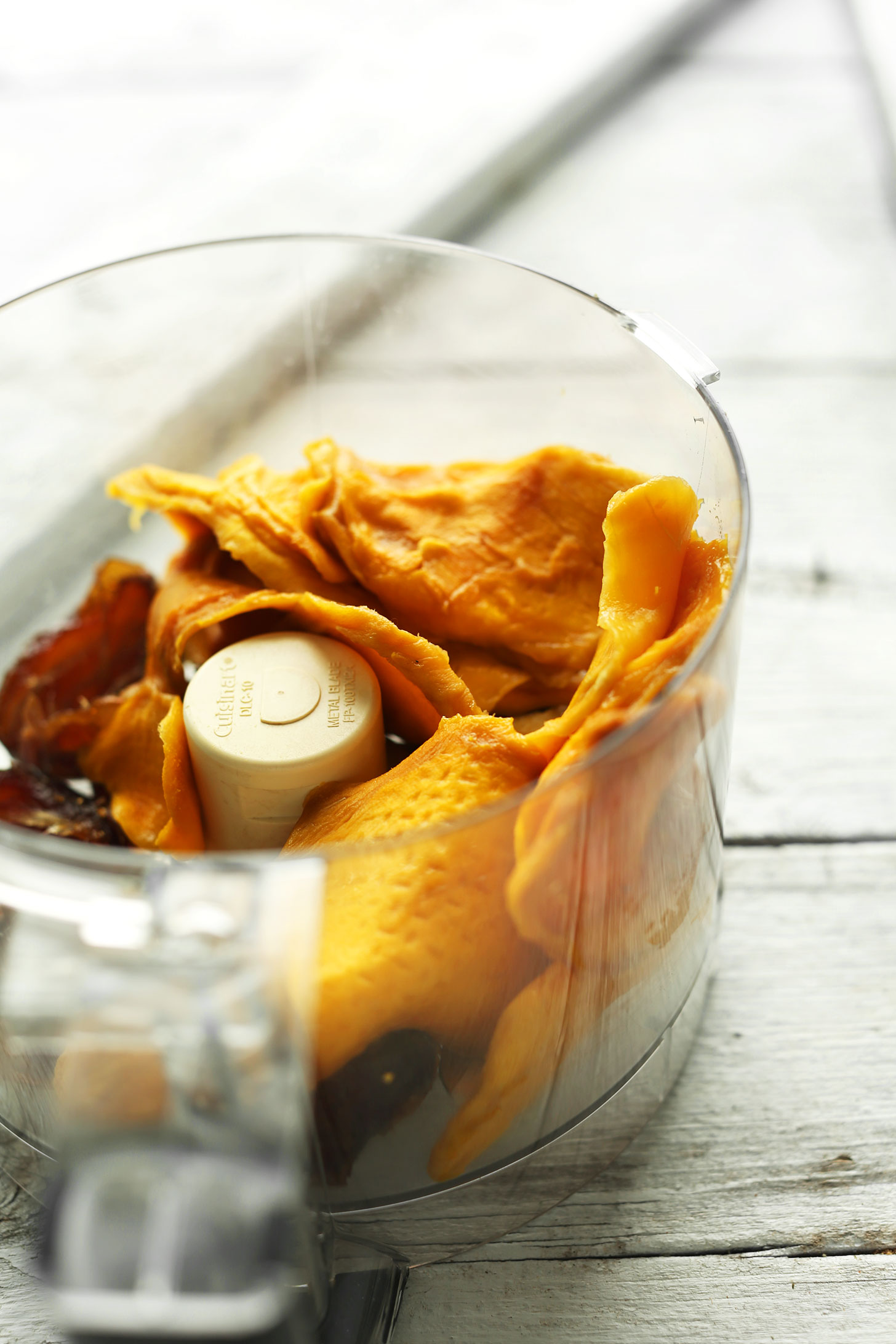 Food processor with ingredients for making fiber- and protein-rich Dried Mango Energy Bites