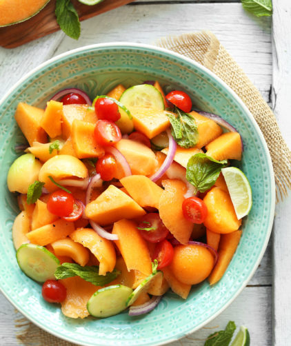 Bowl of our easy vegan summer salad made with Tomato, Cucumber, Cantaloupe, and fresh mint