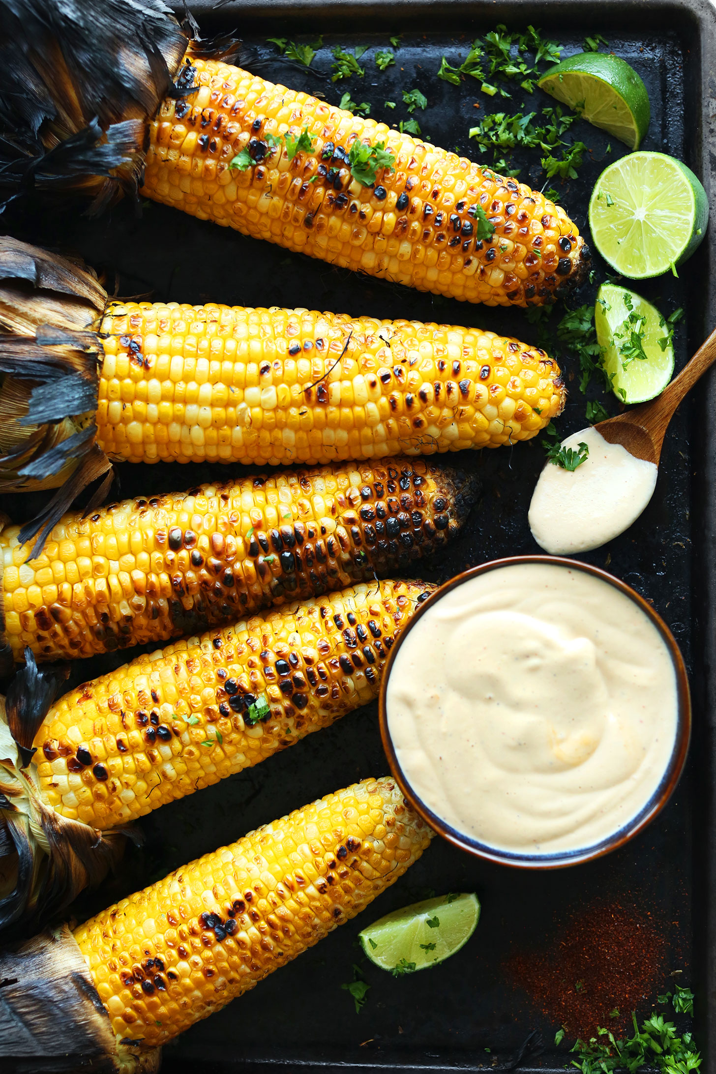 Baking sheet with grilled corn on the cob and sriracha aioli for a perfect summer BBQ dish