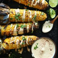 Baking sheet of grilled corn cobs with vegan aioli