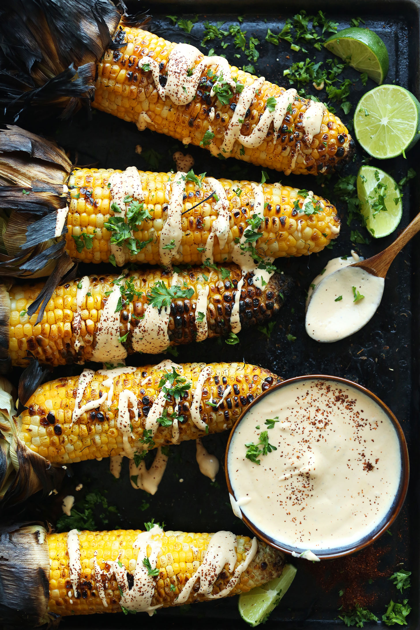 Grilled Corn Cobs drizzled with vegan Sriracha Aioli and fresh cilantro for a summertime recipe
