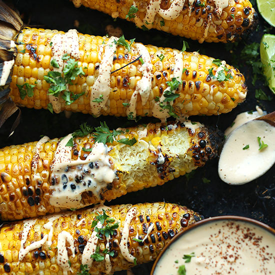 Baking sheet with Grilled Corn drizzled with Vegan Sriracha Aioli