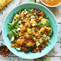 Teal bowl filled with Grilled Corn & Zucchini Salad with Sun-Dried Tomato Vinaigrette