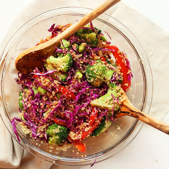 Wooden salad spoons in a glass bowl filled with Asian Quinoa Salad