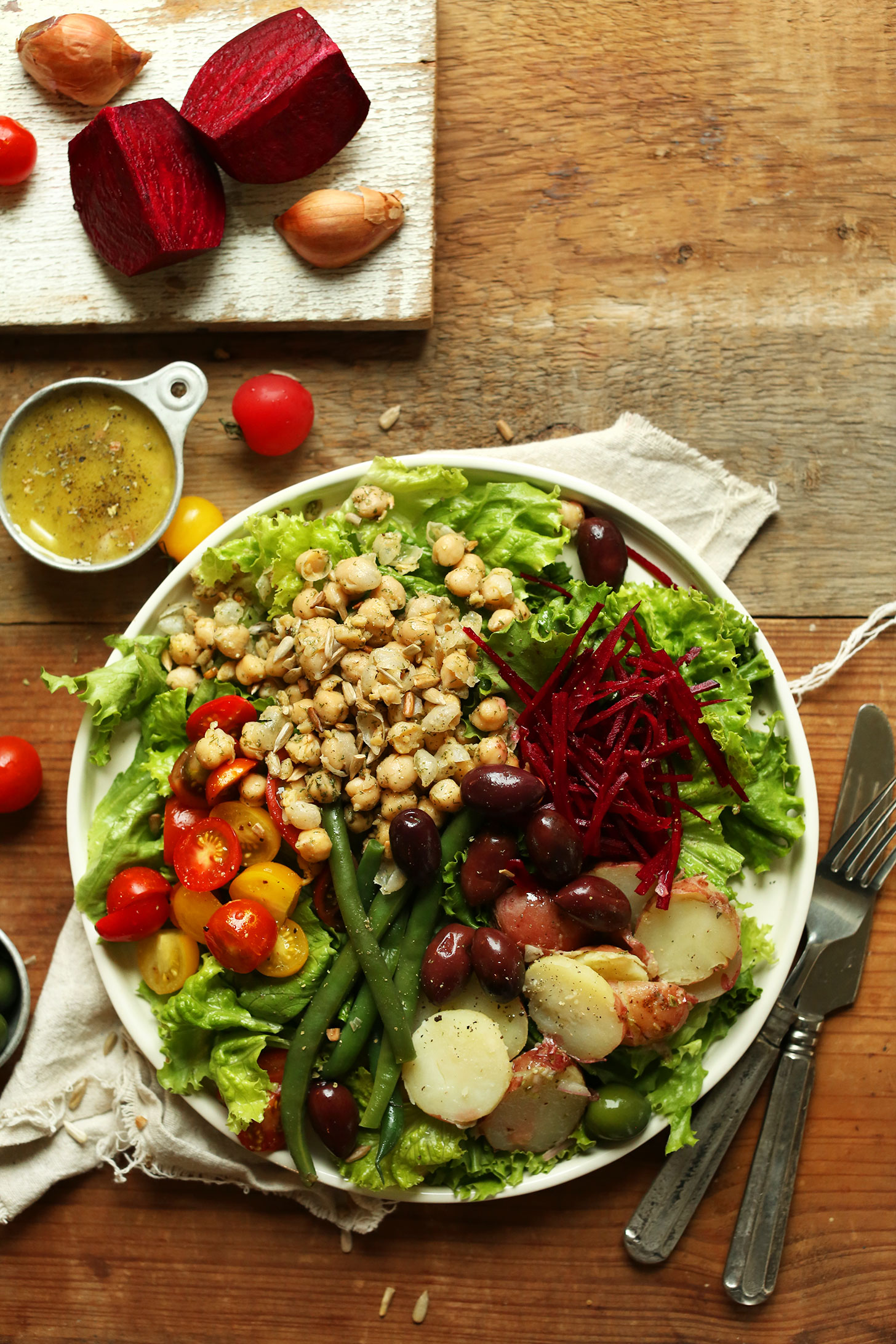 Big Vegan Nicoise Salad with lettuce, shredded beets, olives, green beans, potatoes, tomatoes, chickpeas, and dressing