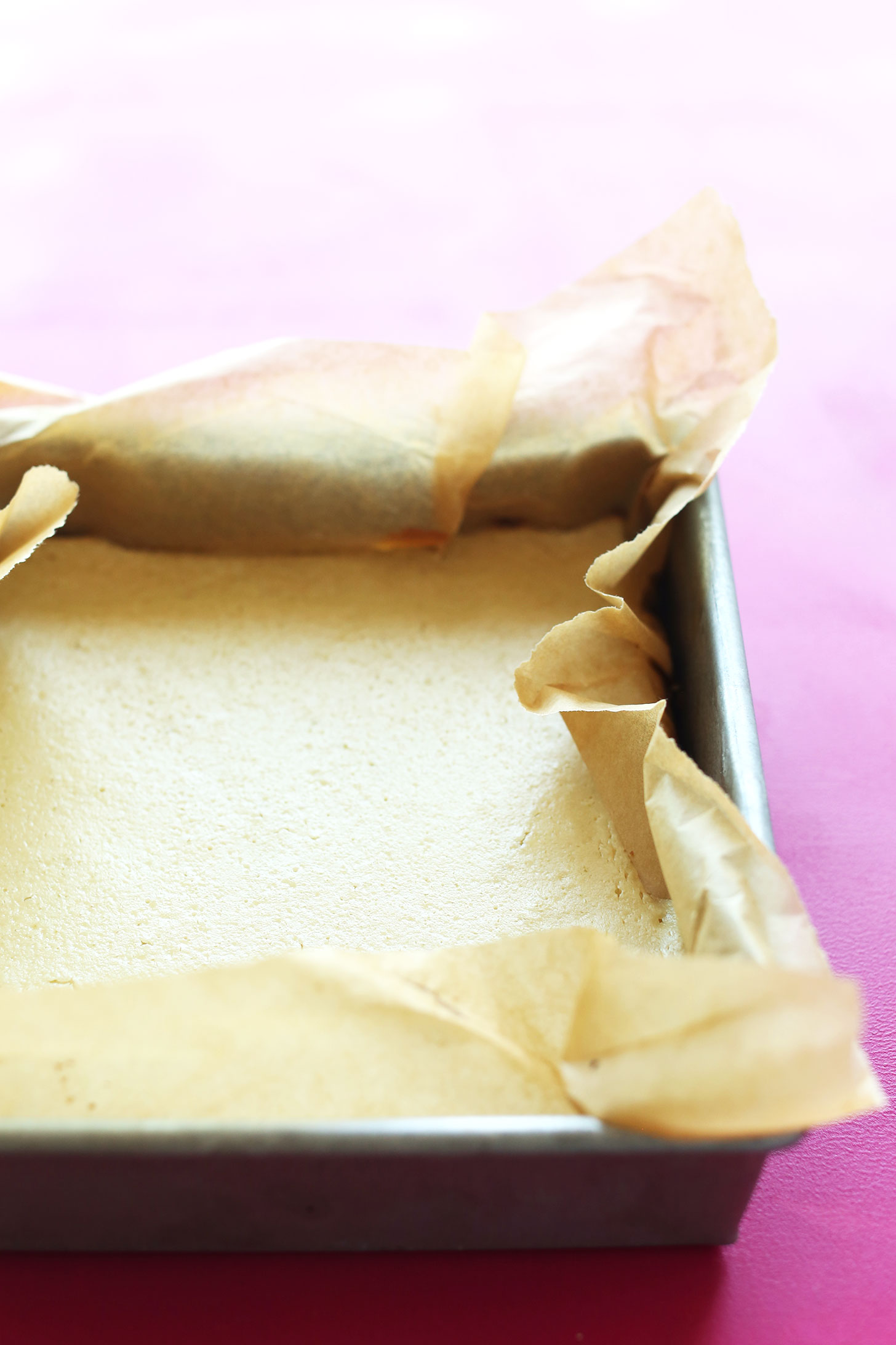 Parchment-lined baking pan filled with our gluten-free vegan Key Lime Pie Bars recipe