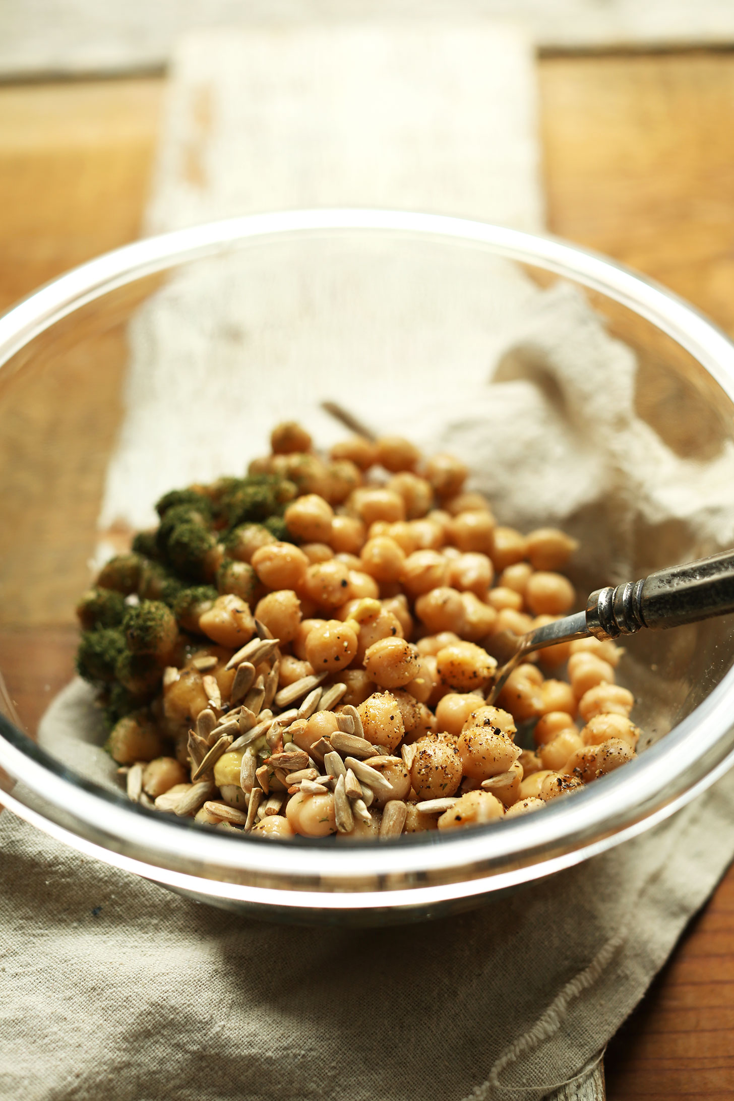 Stirring together chickpeas, sunflower seeds, and dill to make a vegan whole meal salad