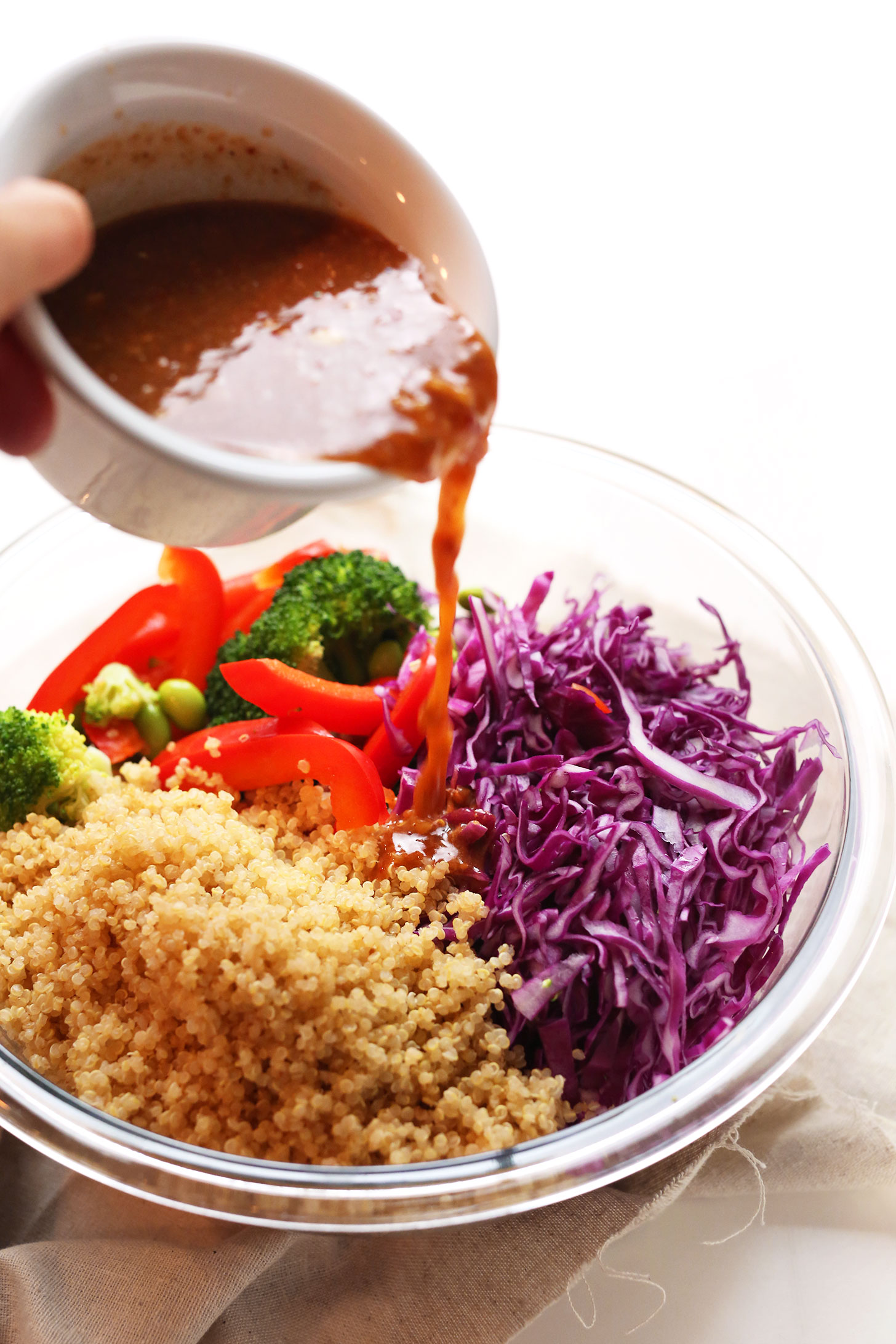 Pouring dressing over our Asian Inspired Rainbow Quinoa Salad for a protein- and fiber- rich plant-based meal