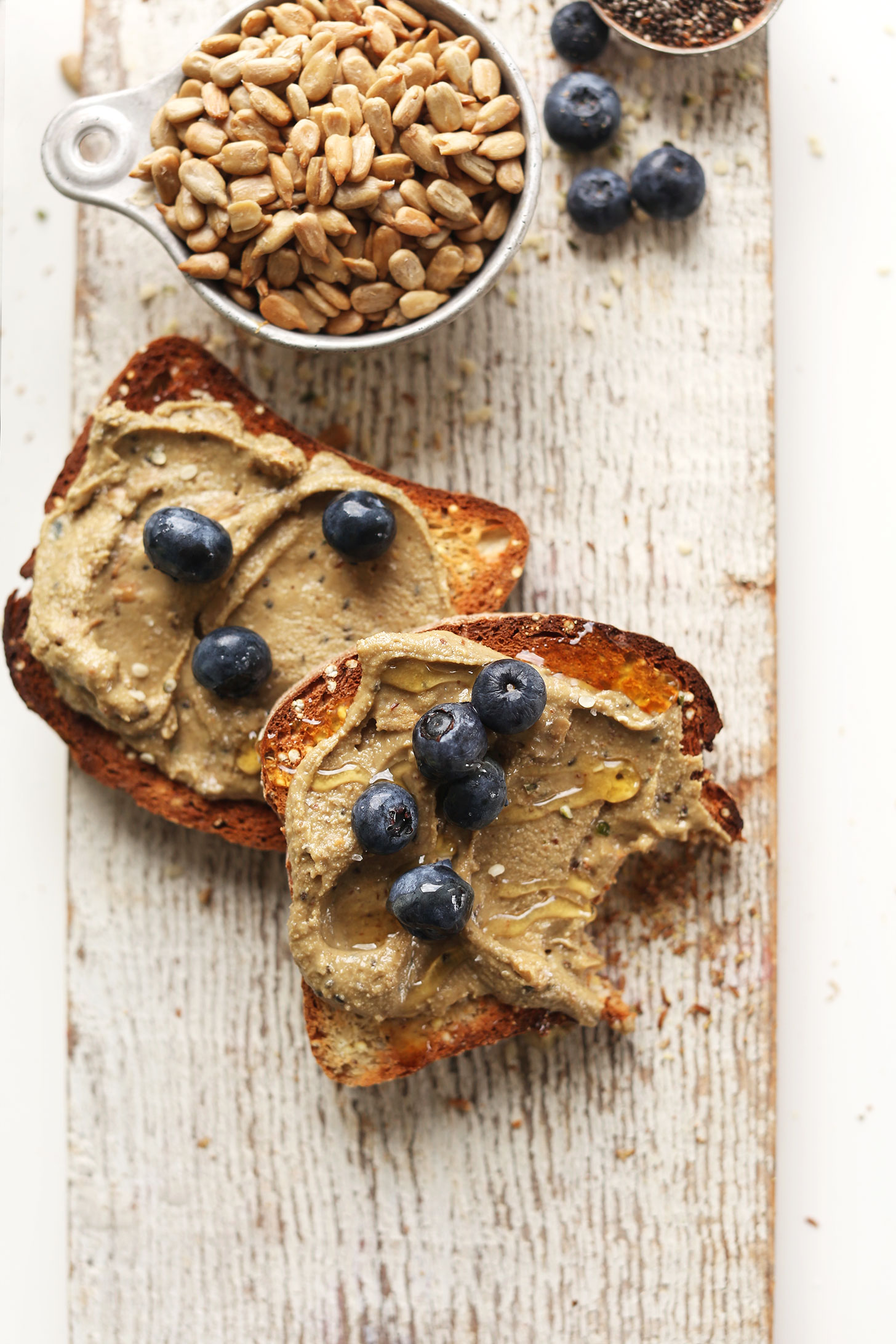 Partially eaten gluten-free toast topped with our Sunflower Seed Butter recipe