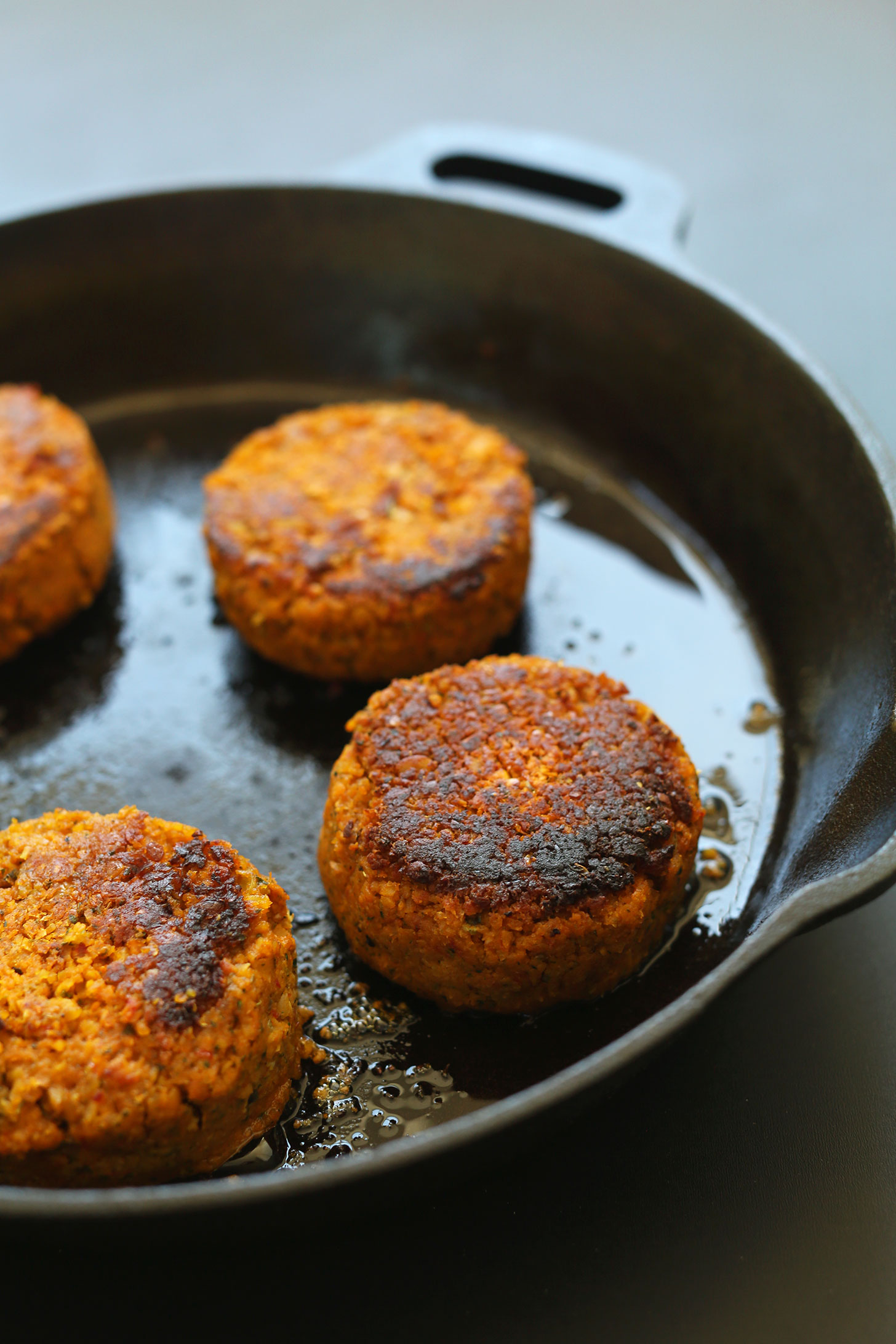 Cooking gluten-free vegan chickpea burgers in a cast-iron skillet
