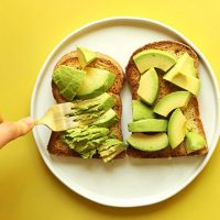 Using a fork to mash avocado on toast