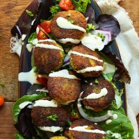 Tray of salad topped with Classic Vegan Falafel and tahini sauce
