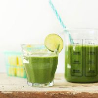 Measuring glass and drinking glass filled with our Ginger Colada Green Smoothie