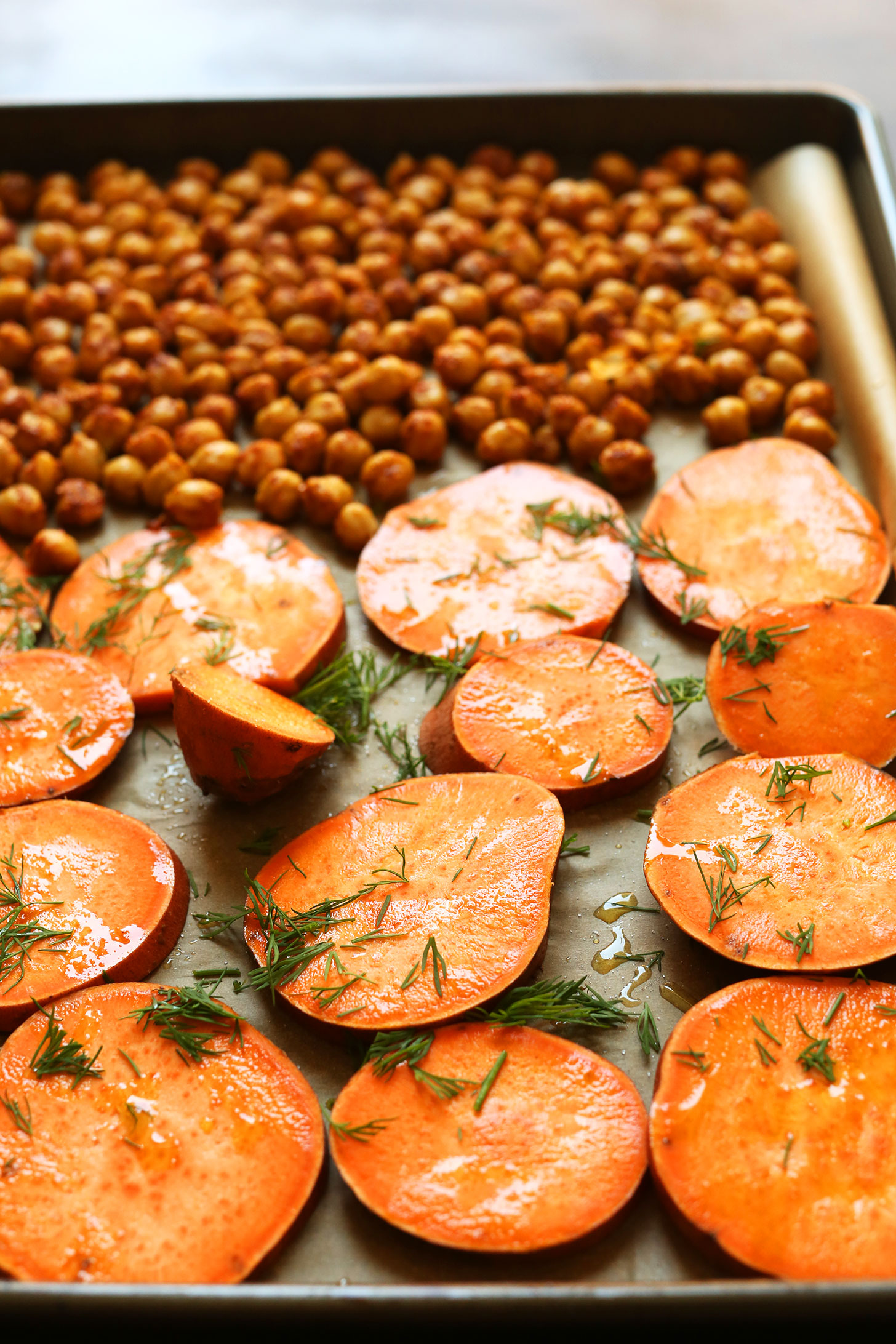 Parchment-lined baking sheet with chickpeas and sliced sweet potatoes topped with fresh dill