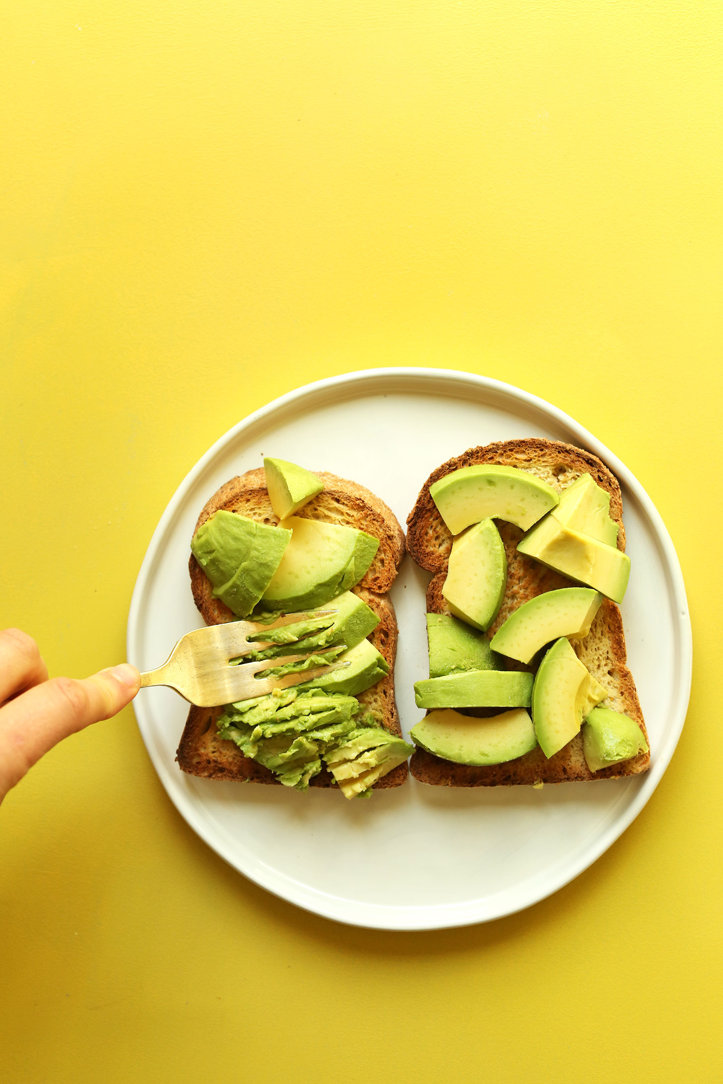 Smashing avocado onto gluten-free bread for the most delicious vegan avocado toast recipe