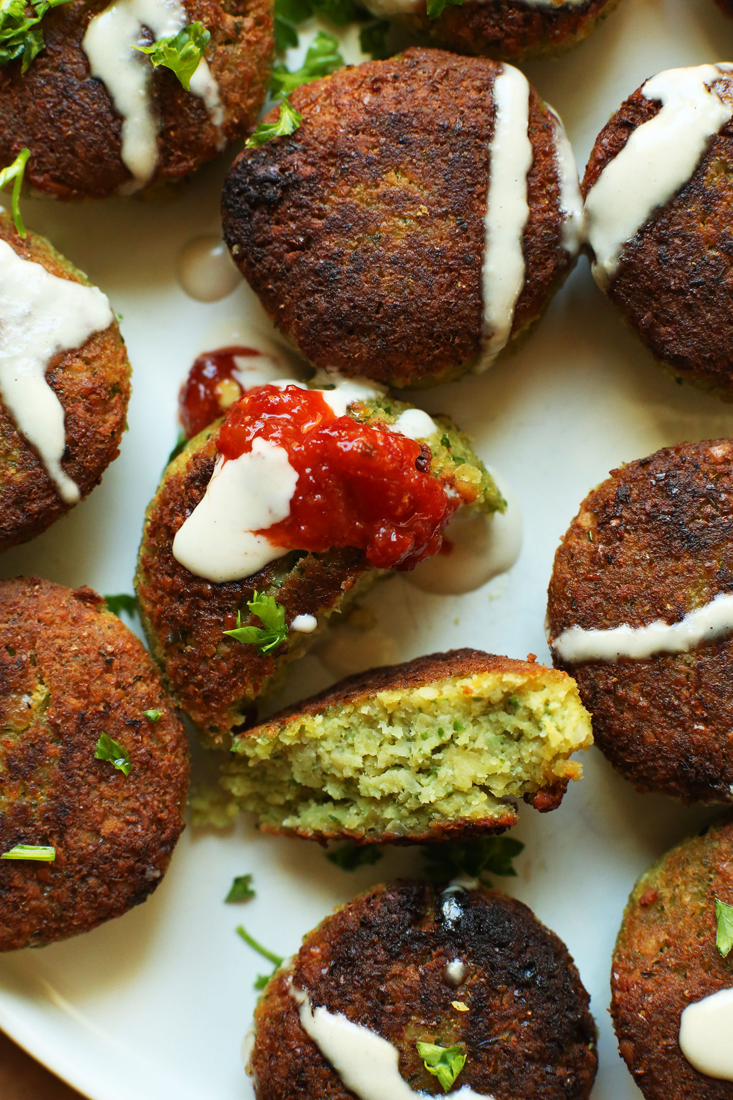 Delicious bites of gluten-free vegan falafel drizzled with tahini sauce