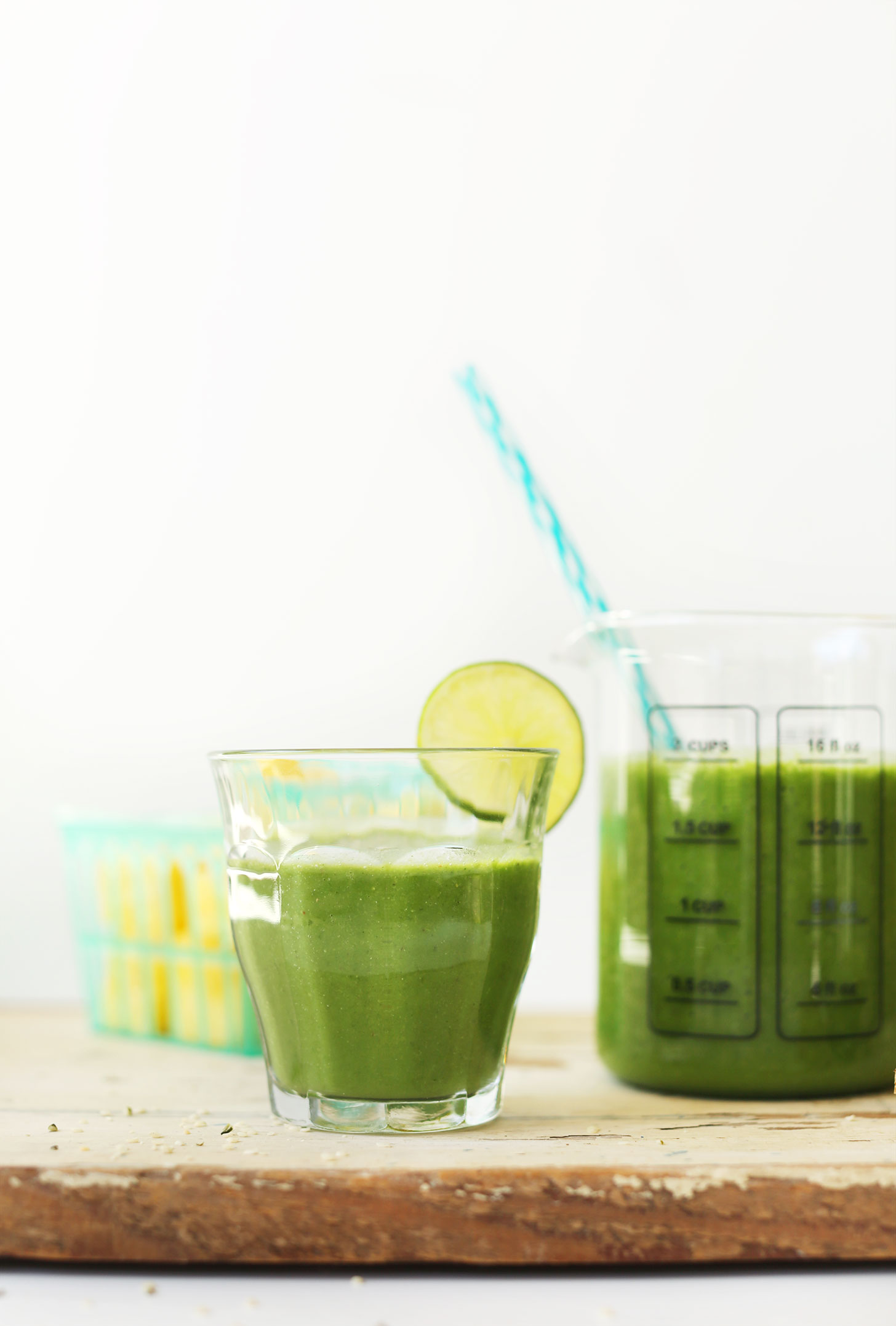 Serving glass filled with Ginger Colada Green Smoothie with a slice of lime on the rim
