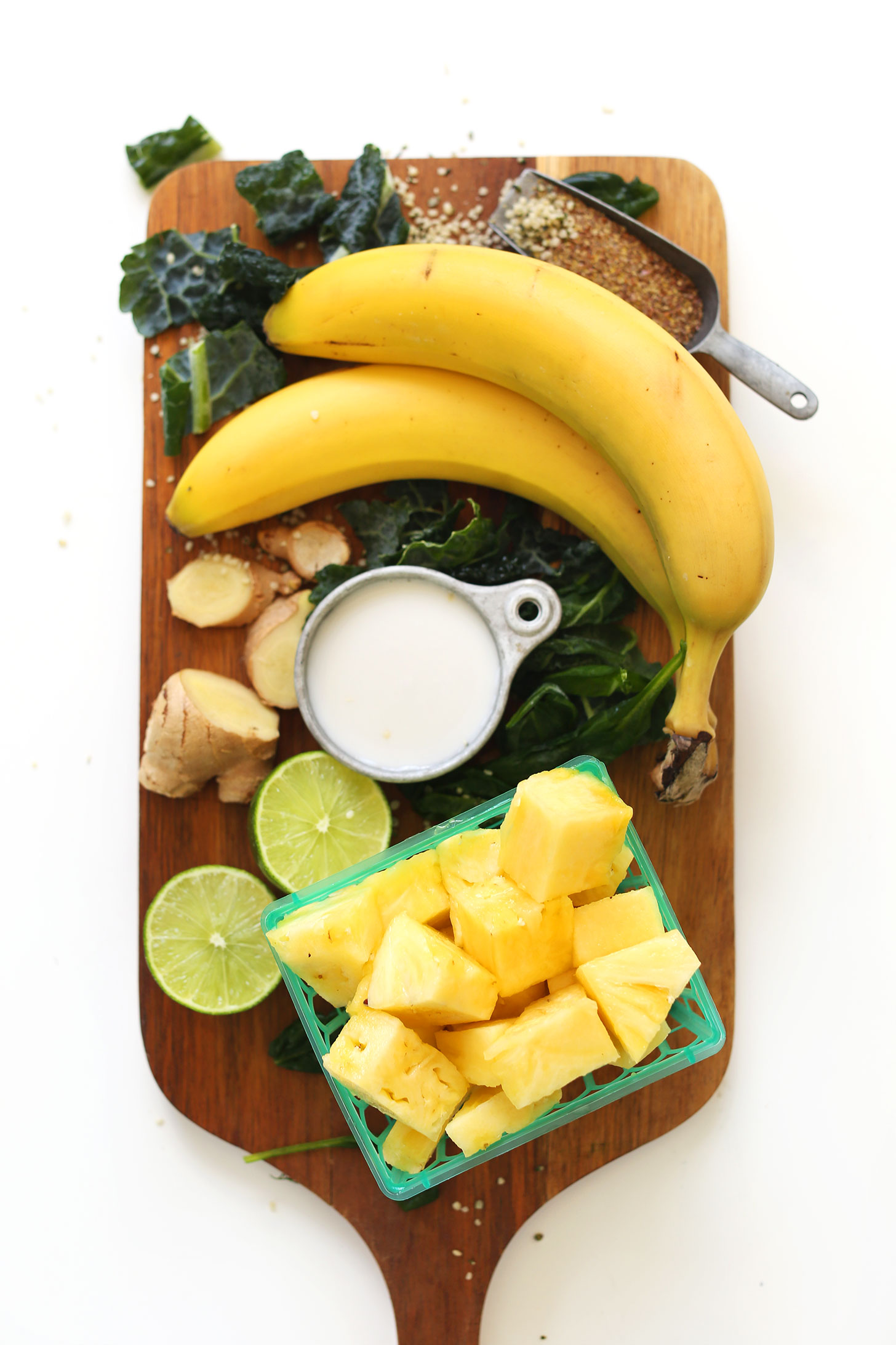 Wood board with pineapple, banana, nut milk, lime, ginger, kale, hemp seeds, and flaxseed meal