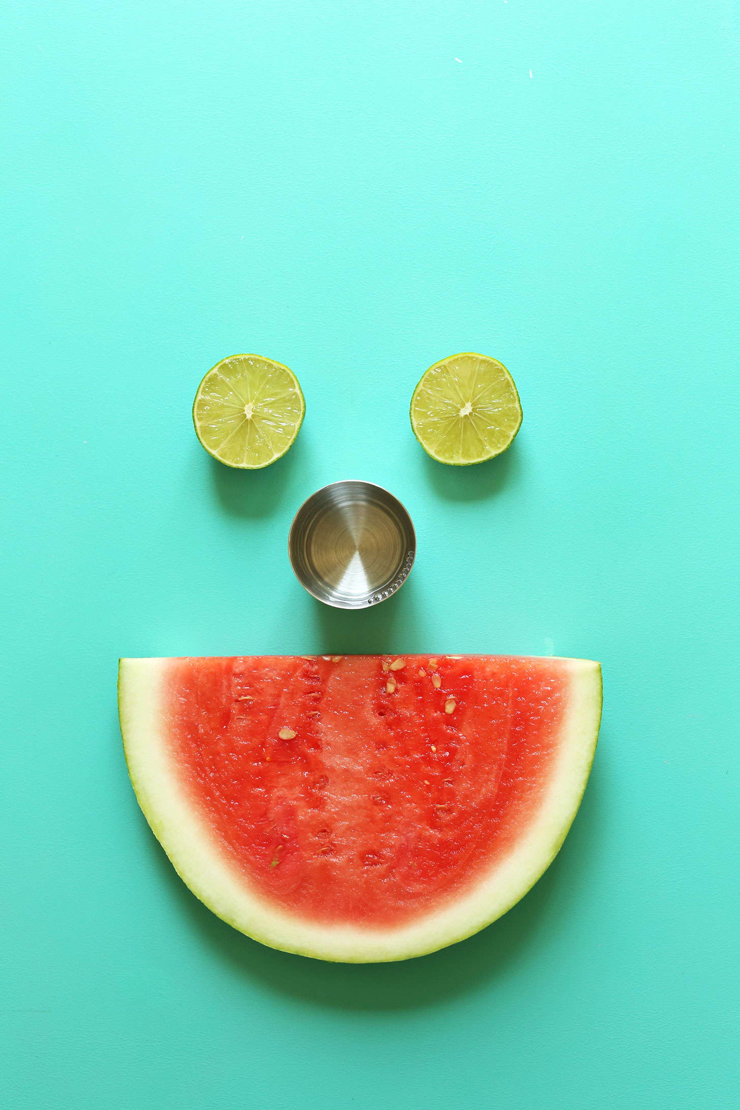 Limes, tequila, and watermelon arranged as a smiley face for Watermelon Margaritas