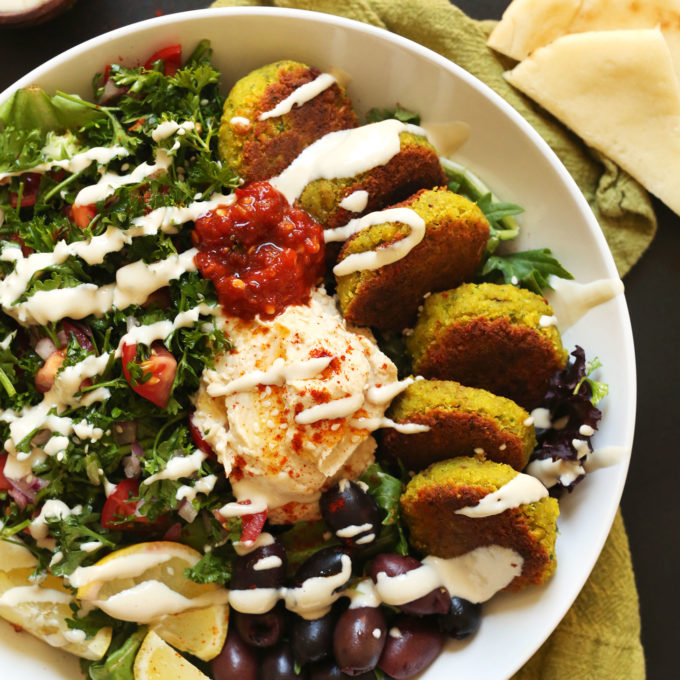 The Ultimate vegan Mediterranean Bowl with hummus, falafel, tahini sauce, olives, and pita