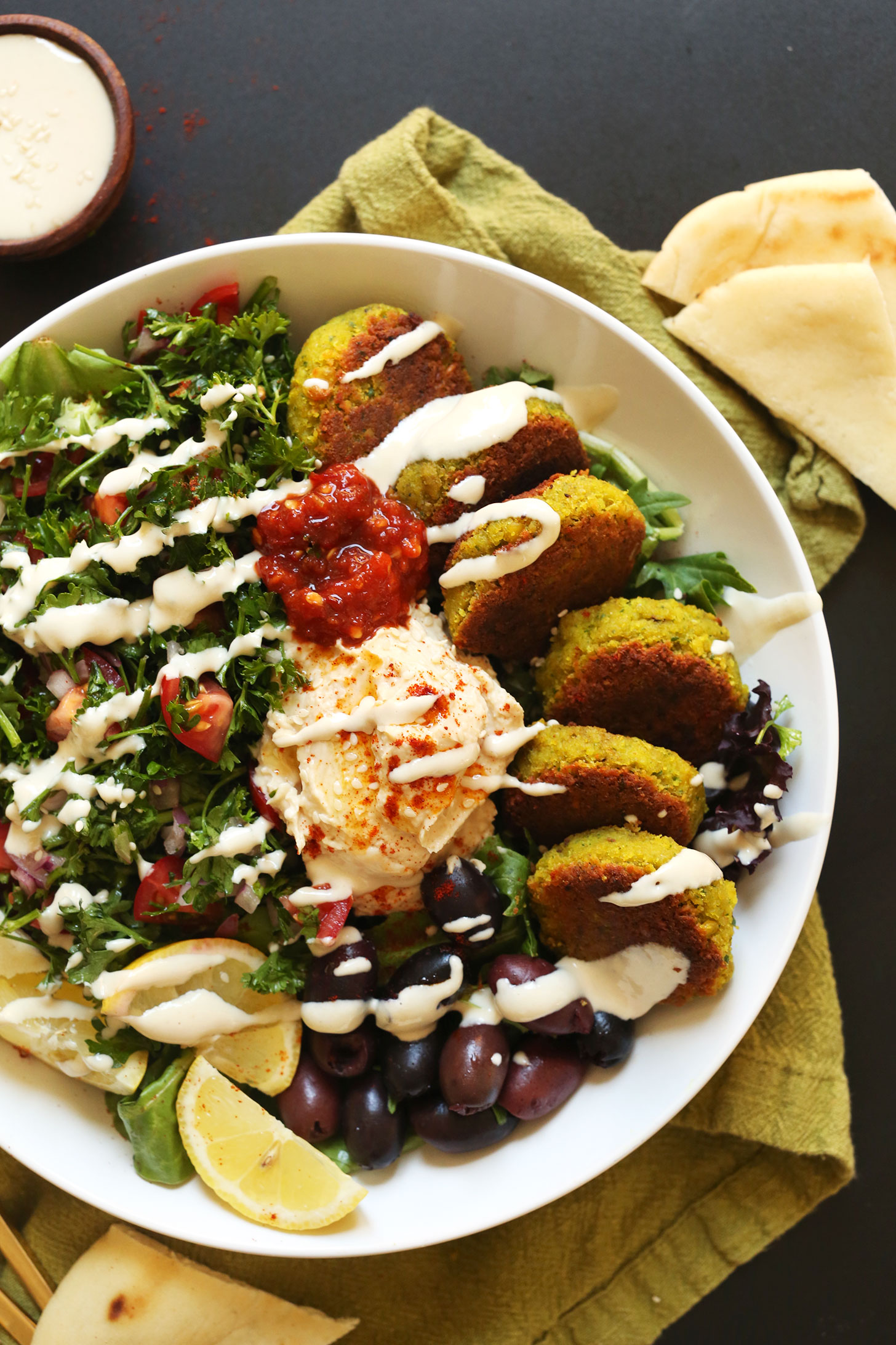 Serving of our vegan Mediterranean Bowl with hummus, falafel, tahini sauce, olives, and pita