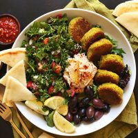 Ultimate Mediterranean Bowl of vegan falafel, pita, tabbouleh, hummus, olives, and lemon slices