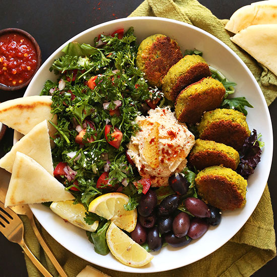 Ultimate Mediterranean Bowl of vegan falafel, pita, tabbouleh, hummus, olives, and lemon slices