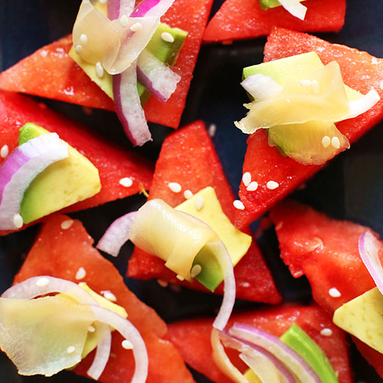 Triangular watermelon slices topped with avocado, red onion, and pickled ginger