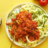 Plate of zucchini noodles topped with Vegan Lentil Bolognese