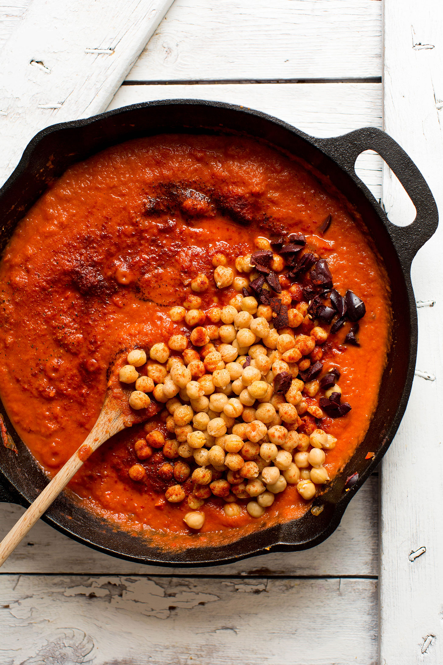 Stirring chickpeas into a cast-iron skillet filled with our gluten-free vegan Shakshuka recipe