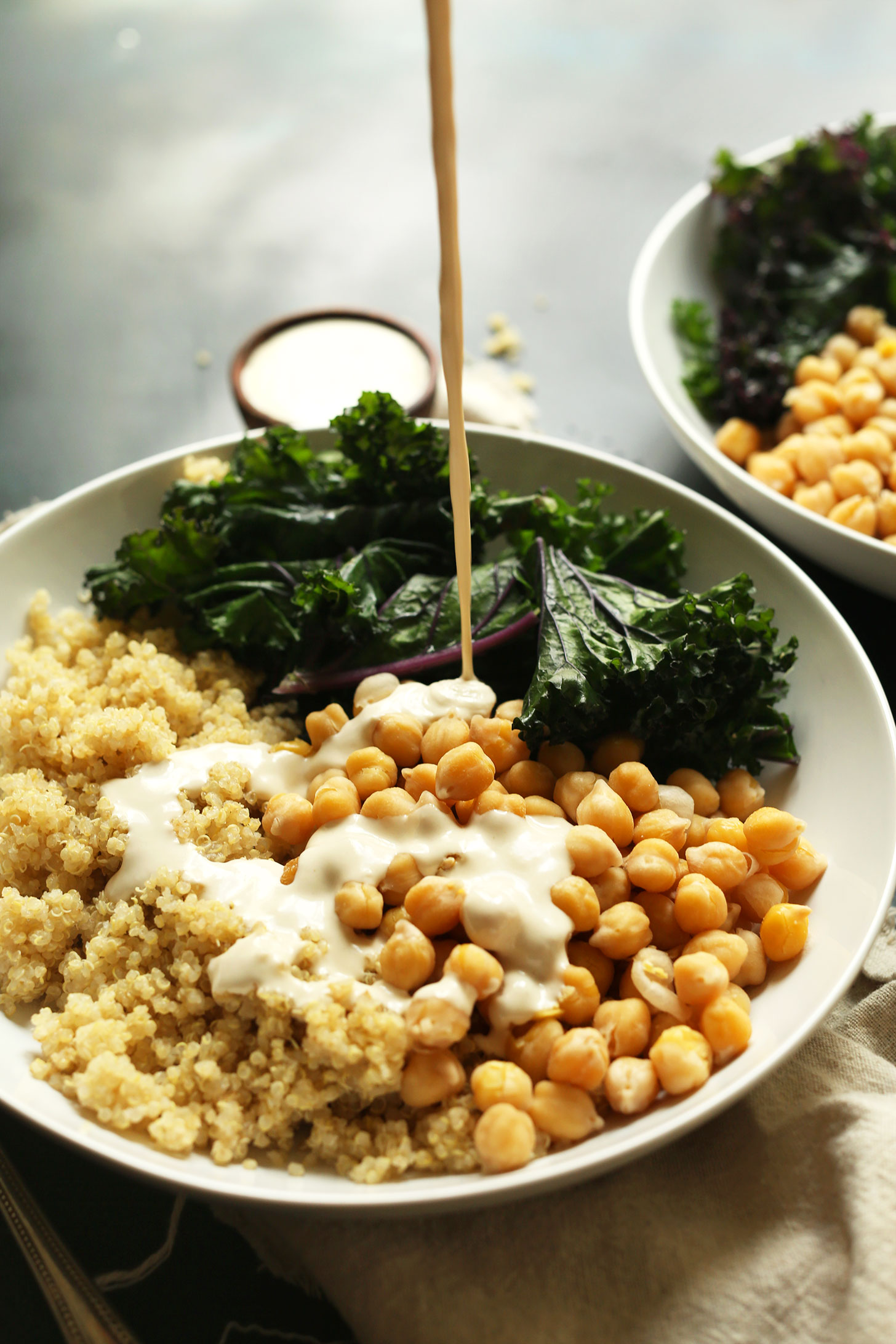 Pouring Tahini Sauce onto our Quinoa Chickpea Buddha Bowls for a simple gluten-free vegan meal