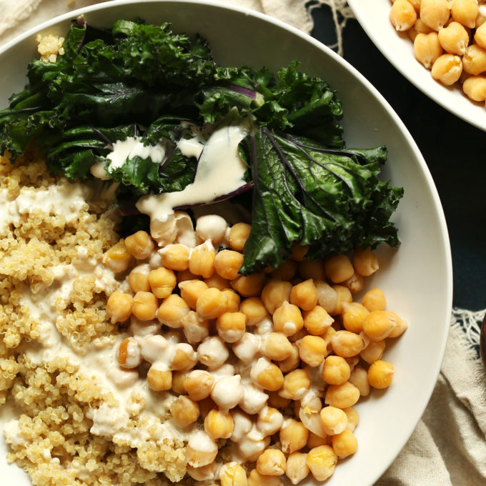 Big bowl of quinoa, chickpeas, kale, and tahini sauce for a delicious gluten-free vegan meal