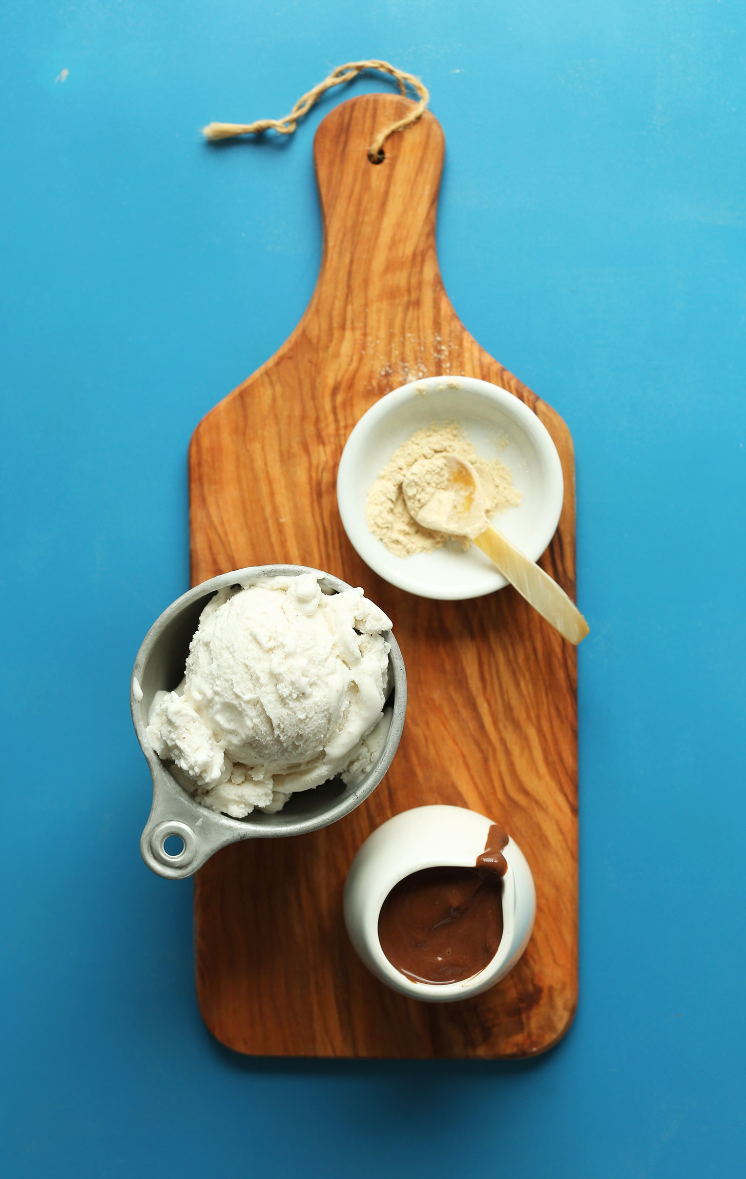 Wood cutting board with maca, vegan ice cream, and chocolate sauce for making a Chocolate Vegan Malt