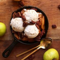 Mini cast-iron skillet filled with cooked apples, ice cream, and pecans