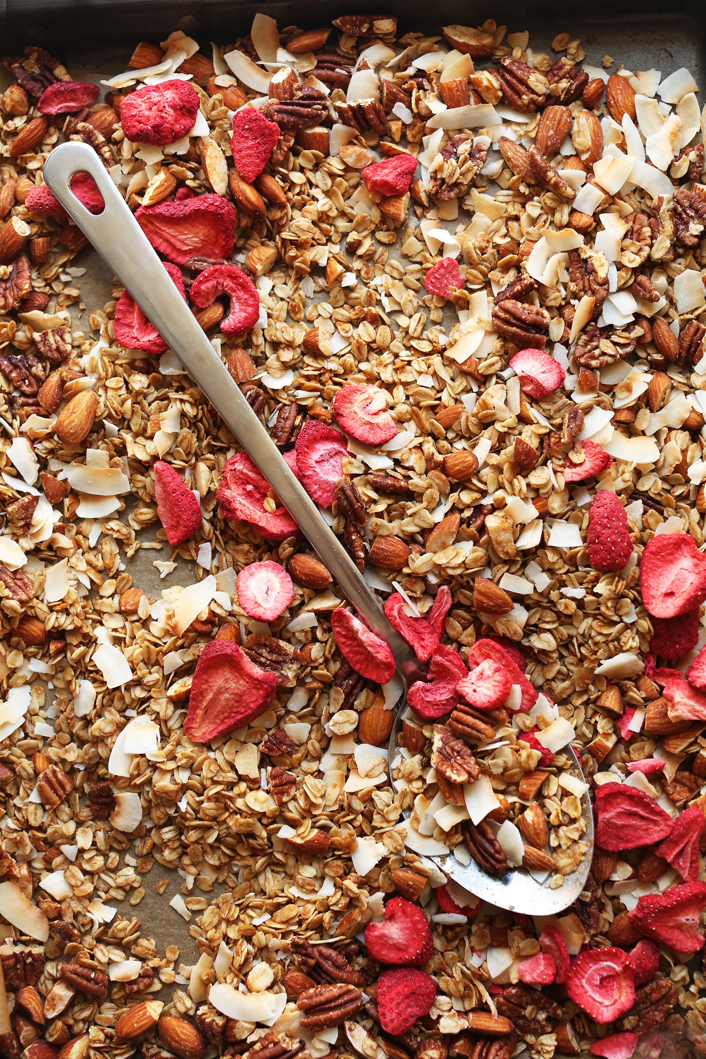 Parchment-lined baking sheet with our gluten-free vegan Coconut Strawberry Granola recipe