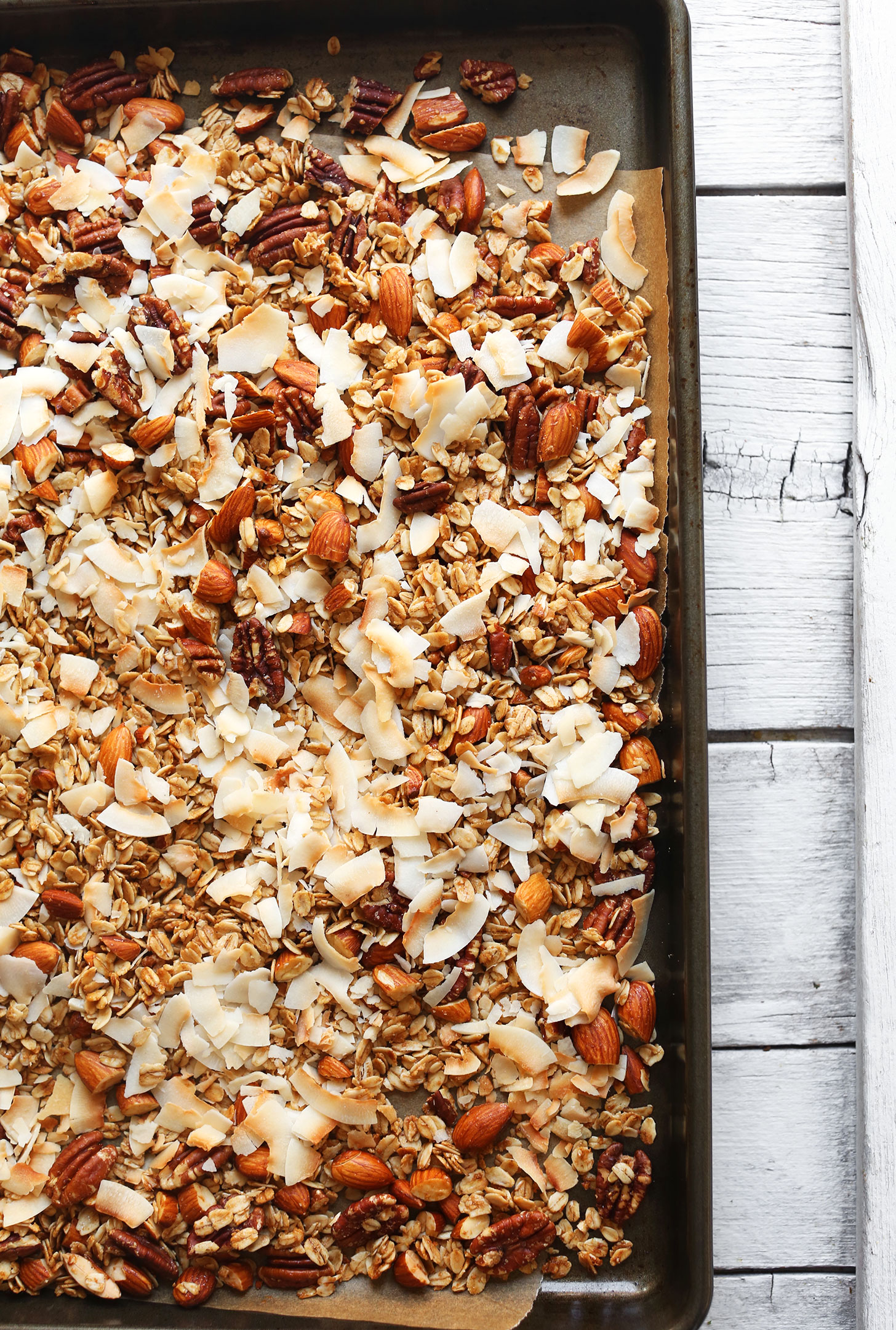 Parchment-lined baking sheet with freshly baked homemade Coconut Strawberry Granola