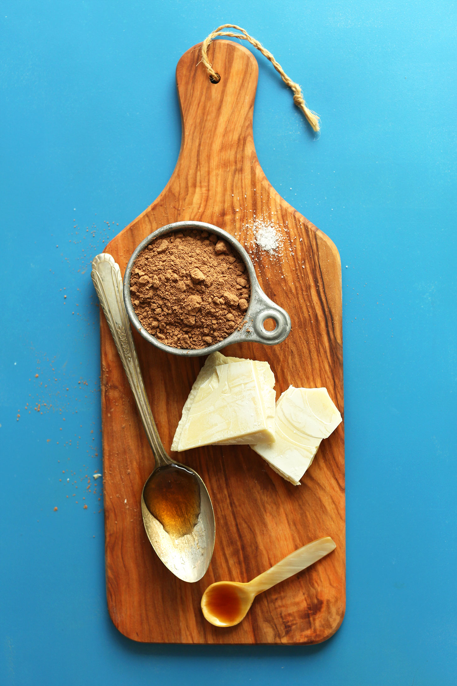 Cutting board showcasing cocoa powder, cacao butter, maple syrup, and vanilla for making homemade chocolate syrup