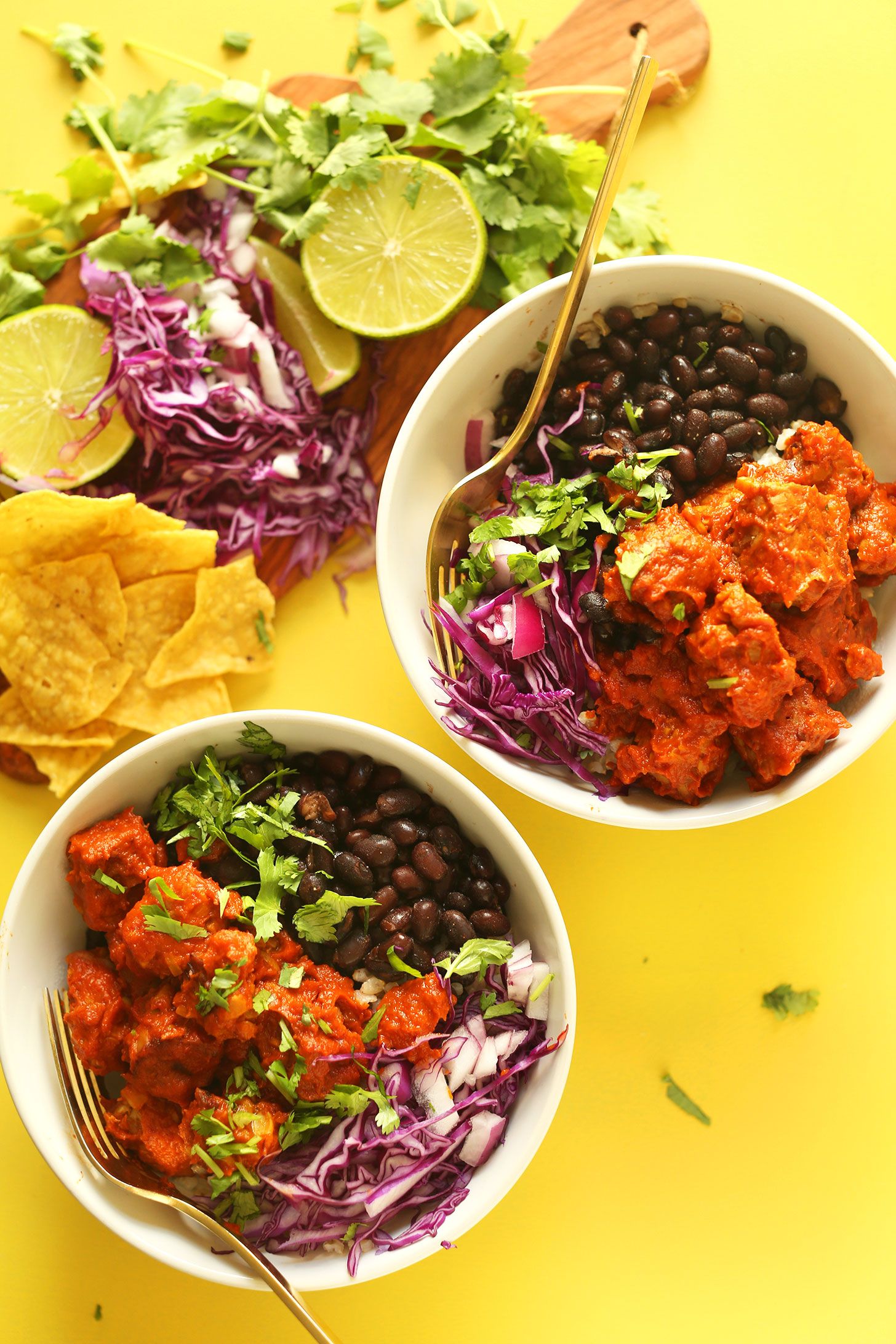 Two servings of our Smoky Tempeh Burrito Bowls recipe alongside ingredients used to make it