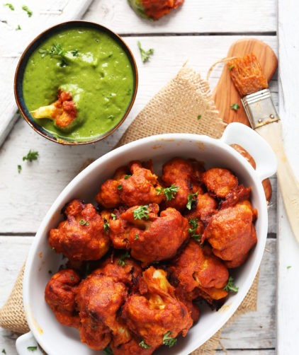 Dipping a vegan Red Curry Cauliflower Wing into Green Chutney dipping sauce