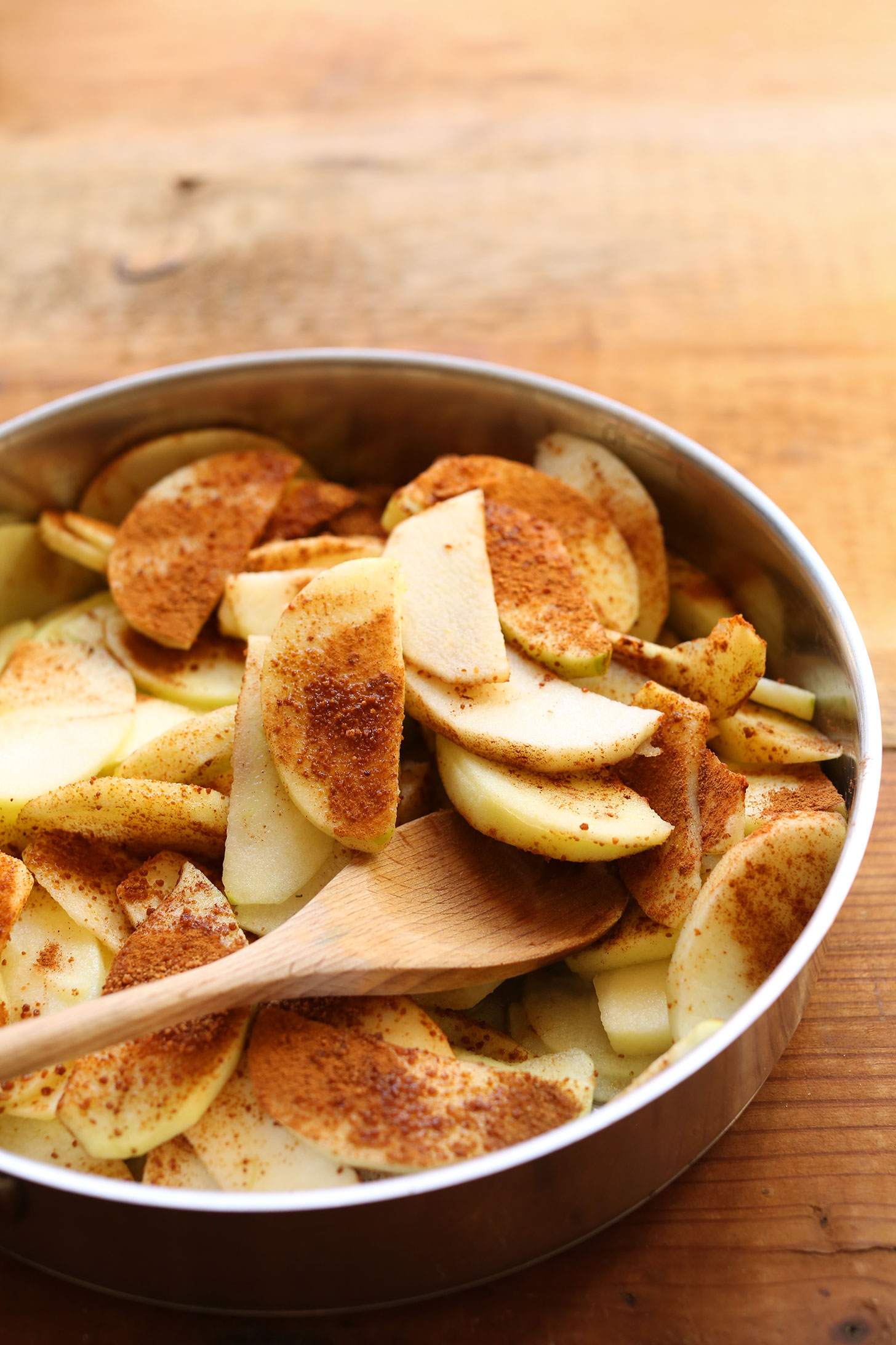 Stirring together a skillet with sliced apples and cinnamon