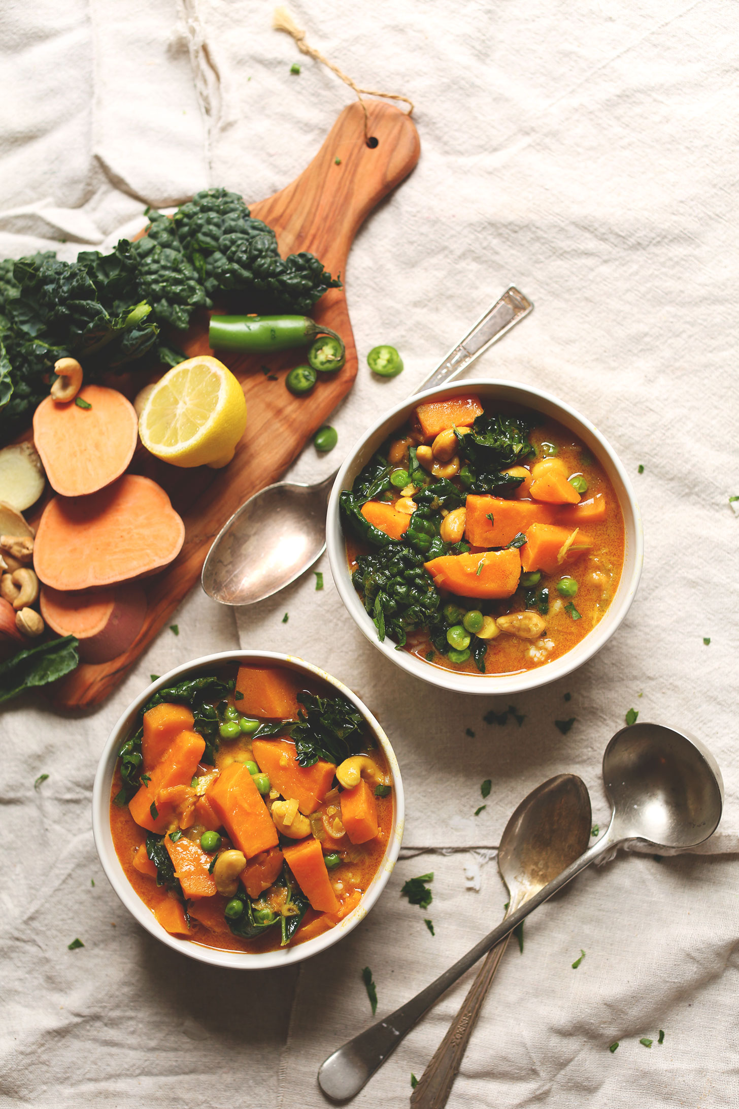 Two big bowls of our Sweet Potato Kale Curry recipe alongside ingredients used to make it