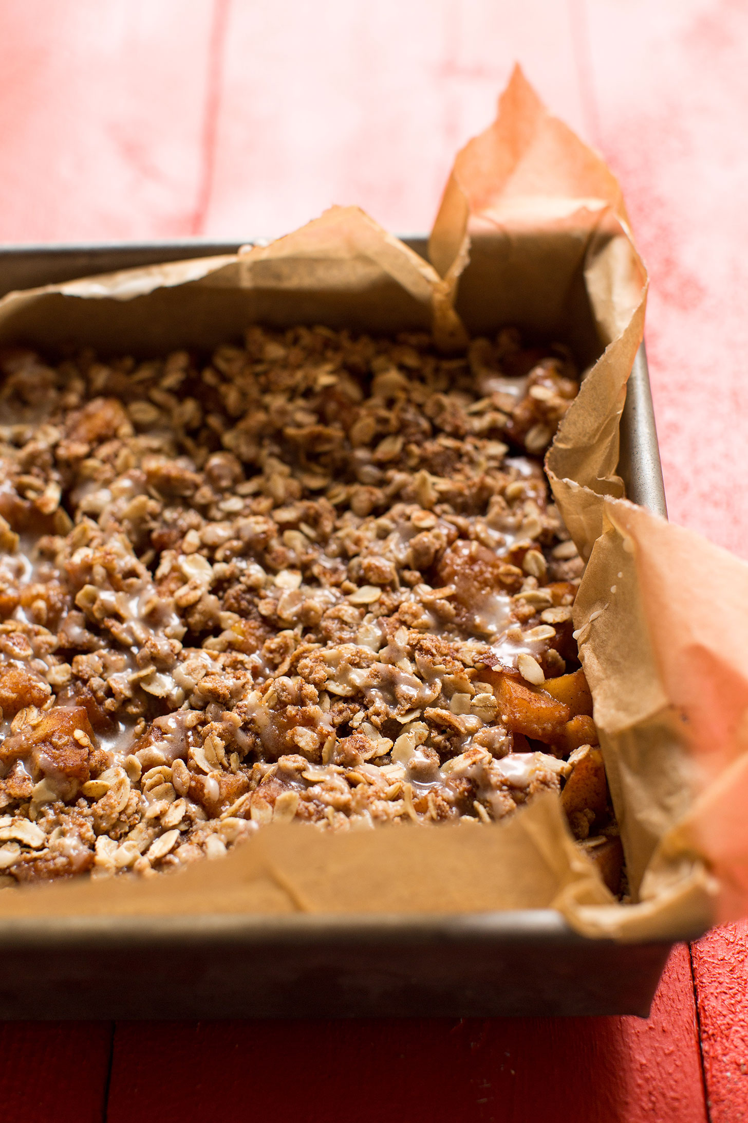 Freshly baked gluten-free vegan Apple Pie Crumble Bars in a parchment-lined baking pan